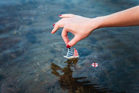 Small toy boat in a female hand above the water on the seashore, concept of vacation, vacation, trip Stockfoto