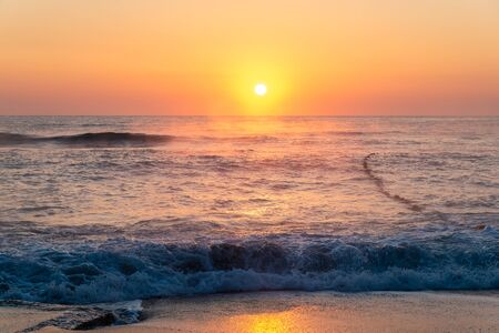 Beautiful sunny dawn in the clear sky on the sea coast during a storm Stockfoto