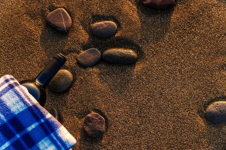 Bottle of wine on a plaid on a sandy beach at sunset, copy space Stockfoto - 137157722