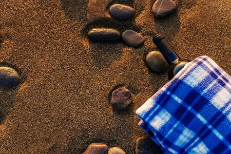 Bottle of wine on a plaid on a sandy beach at sunset, copy space Stockfoto - 137157721