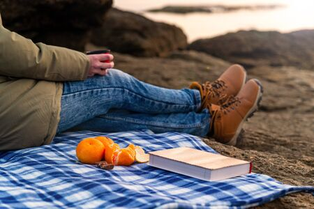 Girl on the beach on vacation on a plaid drinks tea, a book and tangerines in the front pallet, autumn mood