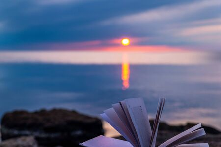 Book by the sea against the blue sunset sky, reading in silence, nobody Stockfoto