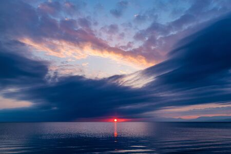 Beautiful red sunset in blue clouds over a quiet sea, sky in reflection of water