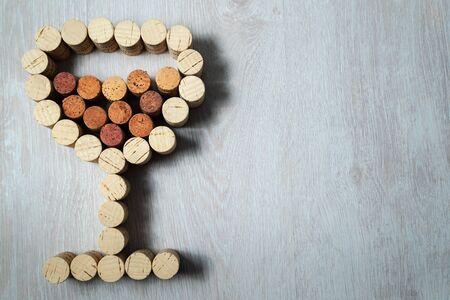 Wine glass laid out from used wine corks on a wooden background
