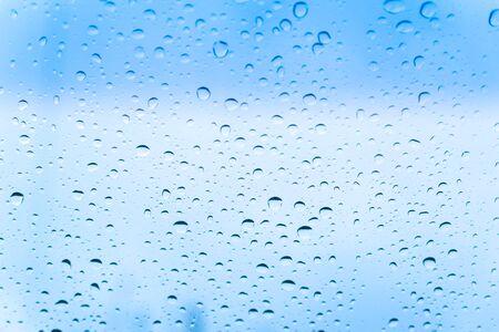 Raindrops on glass against a cloudy blue sky