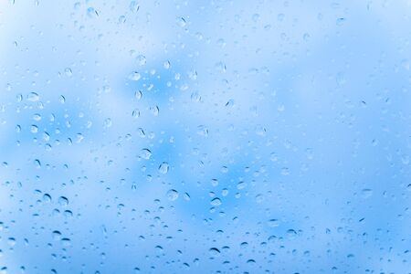 Raindrops on glass against a cloudy blue sky Stockfoto - 136455417