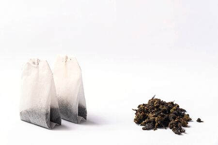 Green tea bags and loose green tea on a white background Stockfoto - 138087670