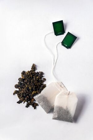 Green tea bags and loose green tea on a white background