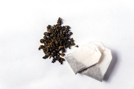 Green tea bags and loose green tea on a white background Stockfoto - 138087672
