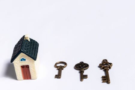 Different keys and a little house on a white background, concept of real estate