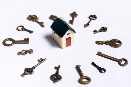 Different keys and a little house on a white background, concept of real estate Stockfoto - 137447189