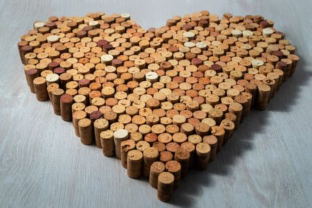 Big heart made of cork wine corks on wooden background, wine design concent Stockfoto - 138087715