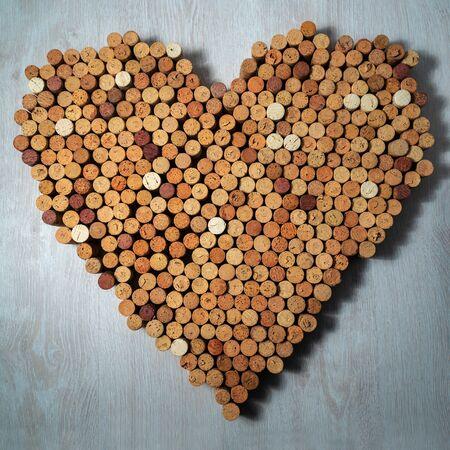 Big heart made of cork wine corks on wooden background, wine design concent Stockfoto - 138087716