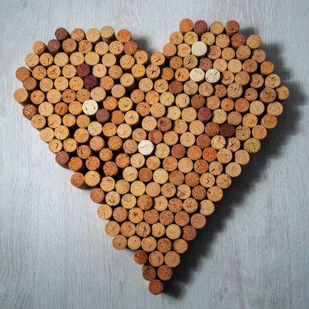Big heart made of cork wine corks on wooden background, wine design concent Stockfoto - 138087719