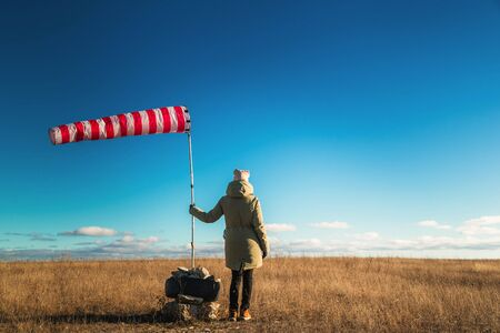 Girl holds a striped weather vane with red and white stripes against a clear blue sky, view from the back Stockfoto - 138087729