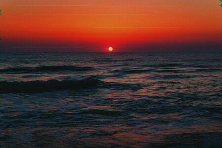 Beautiful sunrise on the sea coast in a storm in glitch effect