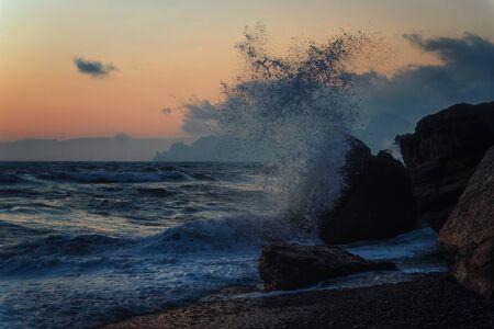 Storm on a rocky sea coast at sunset