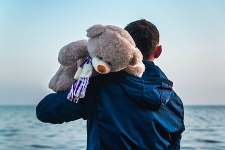 Young man holds a teddy bear in the hands of the sea, a view from the back