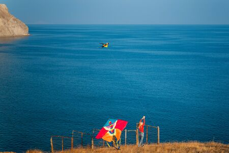 Young girl launches a colorful kite on the sea coast