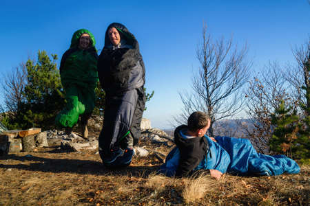 Three tourists in sleeping bags on a hike at a tourist camp early in the morning, funny picture