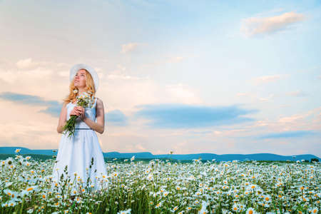Girl in a hat and white dress with a bouquet of white wild daisies in a chamomile field