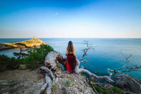 A girl in a black dress on the edge of a cliff against the background of the sea, long hair covers her face, quickly grows her head, fooling around. Beautiful summer landscape Stockfoto