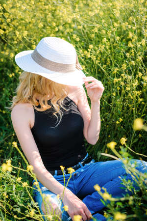 Blonde girl in a black bodysuit with a white hat walks in a rapeseed field, having fun, view from the back Stockfoto