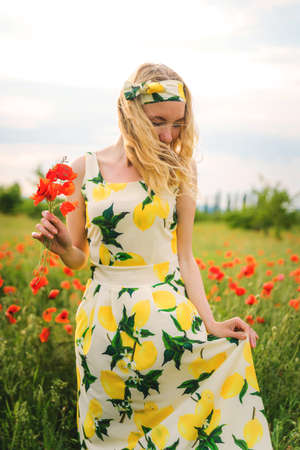 Girl in a hat and dress with a bouquet of poppies in a poppy field Stockfoto