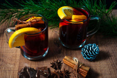 Mulled wine with aromatic spices on a wooden background