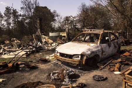 Building and car destroyed by fire. Bushfire aftermath, Australia