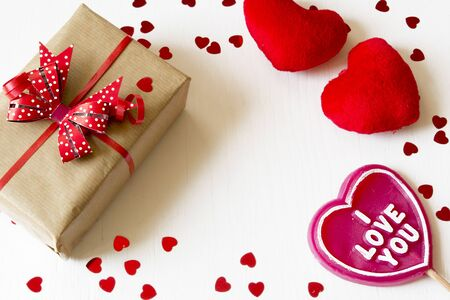 Gift box, fluffy hearts and heart-shaped lollipop wiht I love you text on white wooden background. Copy space.