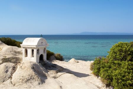 Small typical greek chapel or shrine. blue sky and sea in background. Archivio Fotografico
