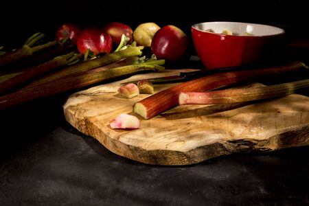 Fresh rhubarb and apples on cutting board.