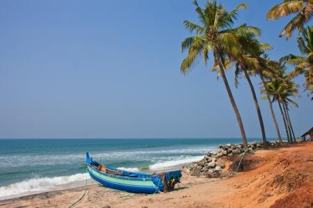 varkala: Blue boat stands on a deserted beach