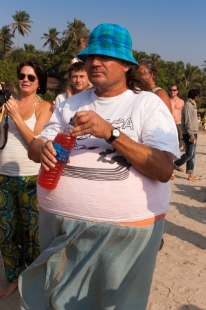 freaks: Arambol, Goa - February 5, 2013  An unidentified man in a fatty suit, with a liter bottle in hand at the annual festival of Freaks, Arambol beach, Goa, India, February 5, 2013  Participants, spectators and all the tourists have fun with a lovely mood