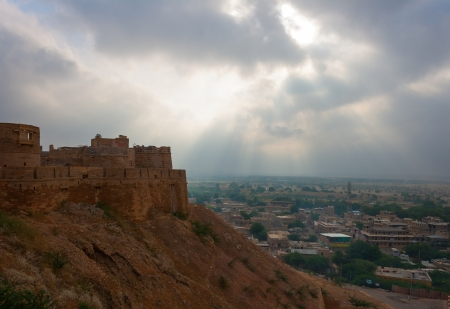 Aerial view of the town and fort of Jaisalmer in the rays from light behind the clouds in cloudy weather  photo