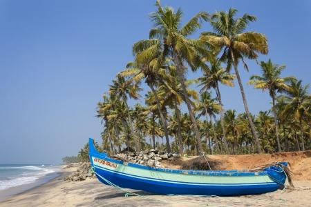 varkala: Blue fishing boat on a deserted beach  Varkala, Kerala, India