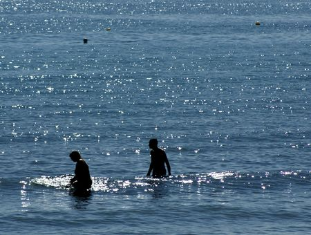People entering the ocean with sparkling water Stock Photo
