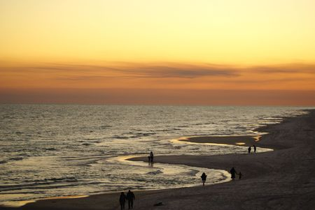 People walking along the sandy beach on the Gulf of Mexico photo