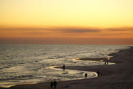 People walking along the sandy beach on the Gulf of Mexico 版權商用圖片