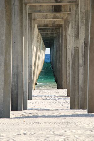 Looking under the broadwalk through to the Atlantic ocean with white sand and the timber photo