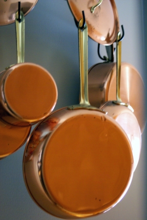 Copper fry pan and pots with lids hanging on a wrought iron hanger