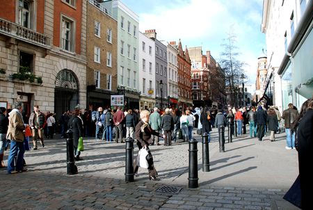 Street close to Covent Garden Market with shoppers and tourists whose faces are blurred and signs changed