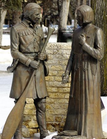 cemetry: Missionary and Voyageur bronze statues in St Boniface Cathedral cemetry representing the early settlement of Canada --specifically Manitoba and the French influence