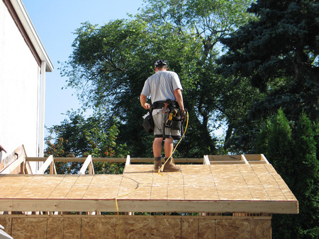 Carpenter working on building a roof for a garage 스톡 콘텐츠