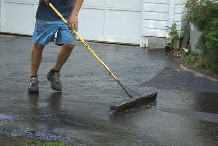 Applying sealer on a driveway