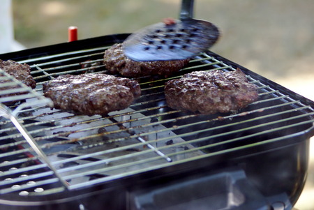 Pressing down hamburger while cooking on a grill Imagens