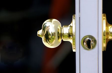 door knob: Shiny brass door knob on door with reflection