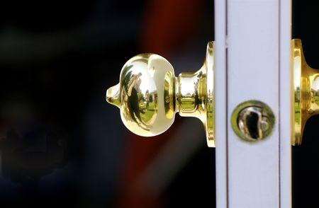 Shiny brass door knob on door with reflection