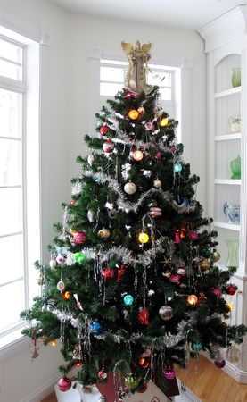 collectibles: Christmas tree decorated in a corner near shelves with collectibles
